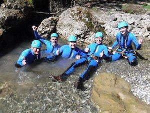 Gruppe im Wasser sitzend in der Schlucht beim Canyoning