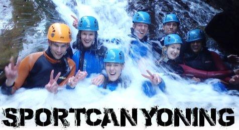 Canyoning Gruppe am Ende eines Wasserfalls im Wasser sitzend