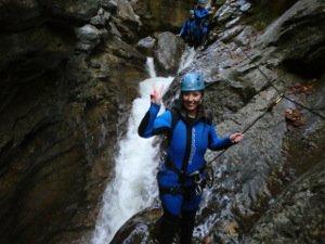 Frau beim Canyoning klettern an der Felswand mit Wasserfall im Hintergrund
