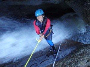 Mädel seilt durch den steilen Wasserfall