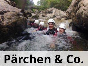 4 Leute beim canyoning im klaren Wasser nach einem Wasserfall in der Schlucht