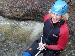 Frau beim canyoning wird in die Schlucht abgeseilt im Gunzesried