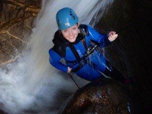 Mädel seilt durch die Schlucht in den Wasserfall