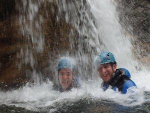 2 lachende Gaeste unter einem Wasserfall in der Schlucht