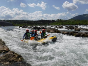 Raftingboot mit gaesten beim Wildwasser paddeln bei Sonnenschein