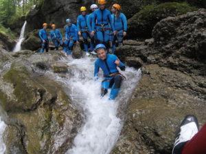Canyoning Gruppe wartet vor einer Naturrutsche in der Schlucht