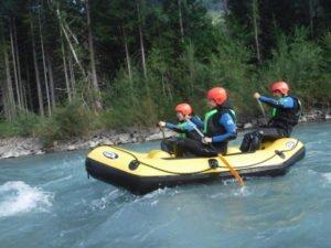 Leute im Raftingboot kurz vor einer Stromschnelle in Sicherheitsausruestung
