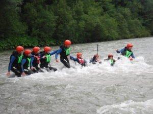 gaeste in einer reihe im Wildwasser im Fluss vor Naturpanorama