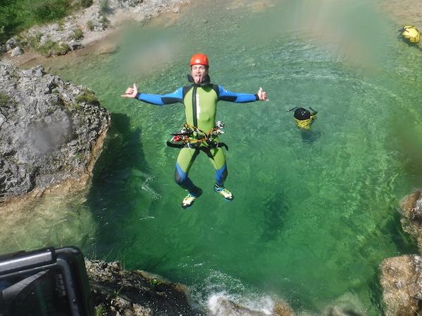 Junge springt in kristallklares Wasser beim canyoning