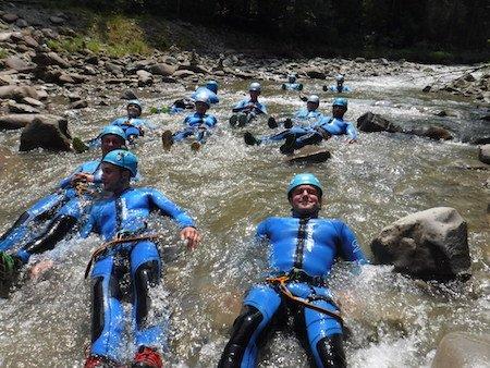 gaeste mit neoprenanzug liegen im Fluss und entspannen