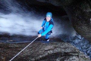 Junge beim Abseilen in die Schlucht am Wasserfall entlang