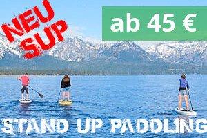 3 Leute auf SUPs auf einem See vor einem Bergpanorama