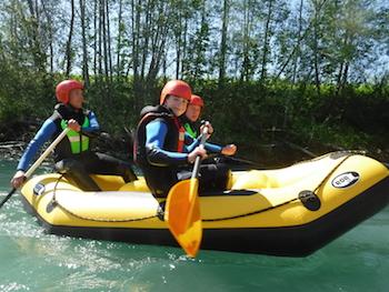 Kinder beim Rafting in der Natur auf tuerkisfarbenem Wasser