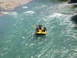 Raftingboot auf tuerkisfarbenem Fluss mit Leuten drin beim paddeln