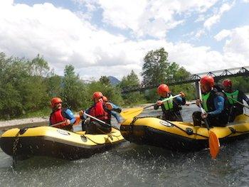 2 grosse Raftingboote mit Leuten bei Spass und action auf dem Fluss