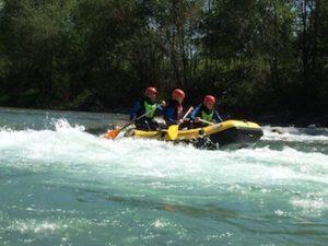 raftingboot auf dem Fluss mit drei leuten drin beim paddeln
