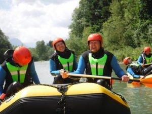 Gaeste mit guter Laune im Raftingboot auf dem Fluss vor Naturpanorama