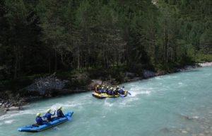 Rafting Boote mit gaesten auf dem Fluss Lech vor einem Wald paddelnd