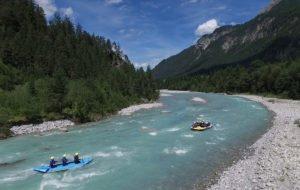 wildwasser Rafting auf tuerkisfarbenem Wasser in natur bei perfektem Wetter