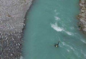 ein gast beim Wildwasserschwimmen in tuerkisfarbenem Wasser im Lech bei Bayern