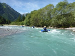Stromschnellen beim rafting auf tuerkisfarbenem Fluss vor Bergpanorama bei Sonnenschein