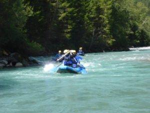 raftinggruppe beim paddeln auf einem kristallklaren Fluss vor natuerlichem Panorama