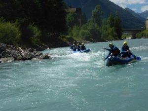 stromschnelle und raftingboote mit Leuten drin beim Paddeln vor Bergpanorama