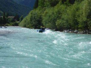 raftingboot im tuerkisfarbenem Wasser im Wildwasser in natuerlicher Umgebung