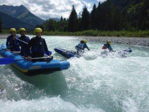 raftingboote im Wildwasser mit paddelnden Gaesten vor Bergpanorama
