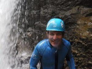 Mann unter Wasserfall in der Schlucht lacht in die Kamera