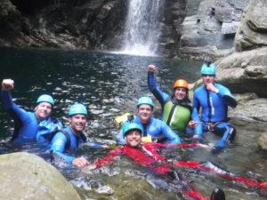 Canyoning Gruppe im Wasser liegend vor einem Wasserfall