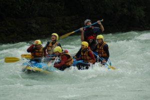 Wildwasser rafting mit einem Boot und lachenden Gaesten