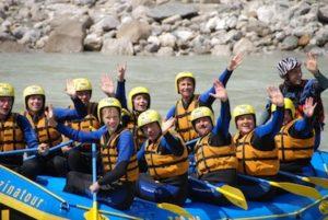 viele Kunden im Raftingboot happy in die kamera winkend