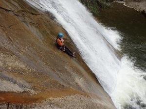 Gast rutscht die finale Rutsche in einem Wasserfall in der starzlachklamm