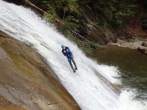 Junge rutscht die finale Rutsche in einem Wasserfall in der starzlachklamm
