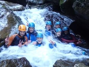 Canyoning Gruppe im Wasser eines Wasserfall sitzend