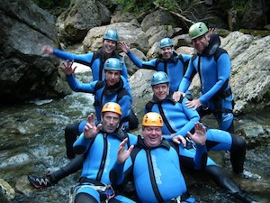 Canyoning Gruppe im klaren Wasser sitzend und winkend