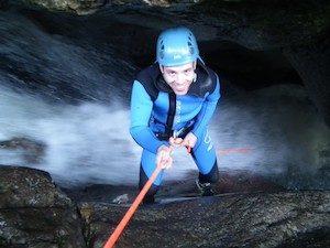 Mann wird abgeseilt mit Helm und sicherheitsausruestung in den Wasserfall
